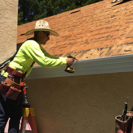 Element Roofing Livermore worker installing a gutter on a home